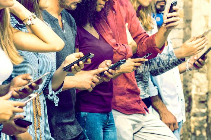 Jóvenes conectados continuamente al móvil
